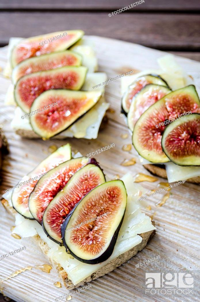 Stock Photo: Bruschetta toasted sliced sourdough bread with cheese and figs drizzled with honey on a white wooden serving board on a wooden table.