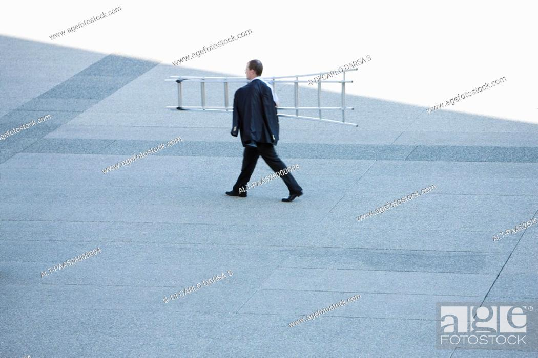 Stock Photo: Businessman carrying ladder on shoulder across public square.
