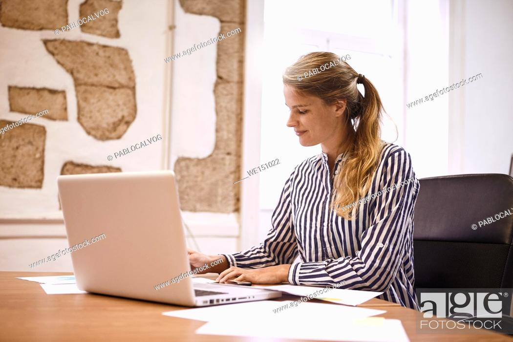 Stock Photo: Professional young woman preparing for meeting making notes from her laptop while wearing a striped formal blouse and her hair tied up.