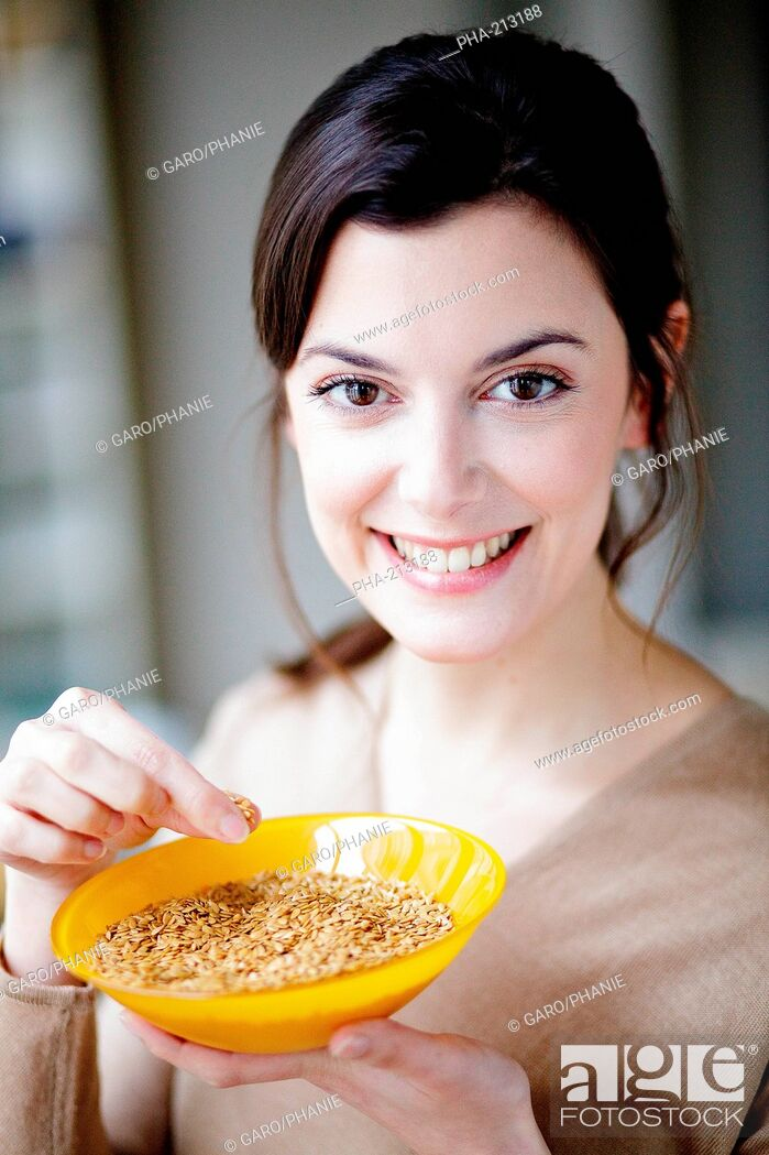 Stock Photo: Woman eating golden flax seeds.