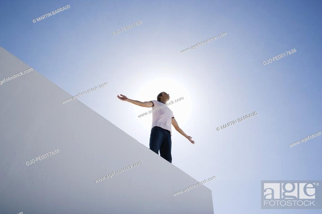 Stock Photo: Man standing on wall with arms up and blue sky.