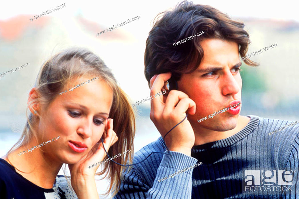 Stock Photo: Young couple sharing headphones.