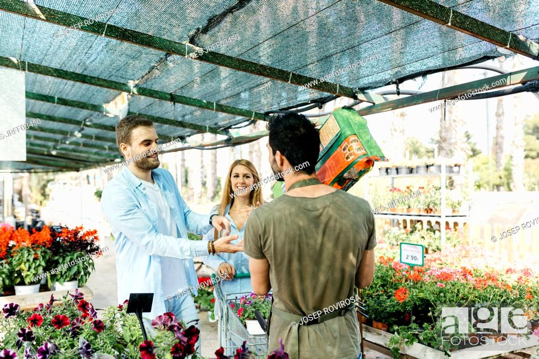 Stock Photo: Worker in a garden center handing over soil to customers.