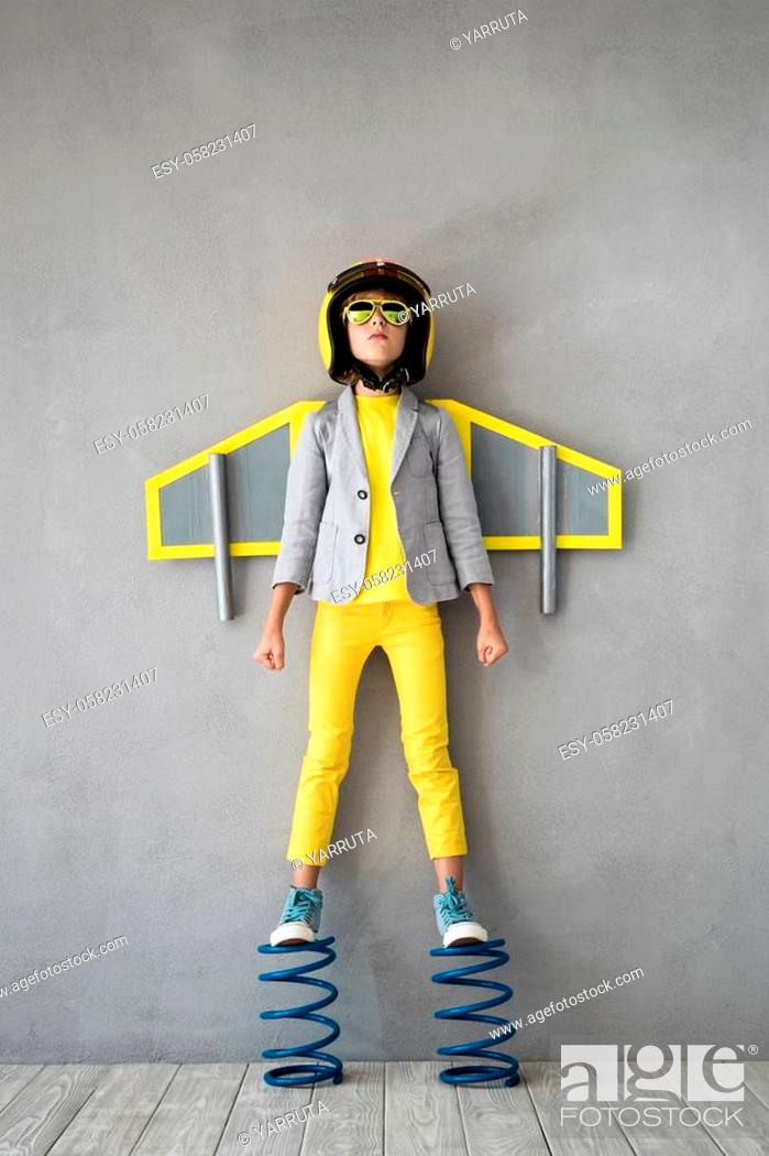 Stock Photo: Happy child playing with toy jetpack. Kid pilot standing on spring. Success, innovation and leader concept.