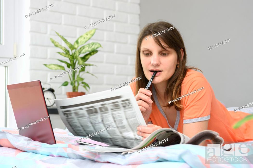 Stock Photo: A girl looks in the newspaper job ads.