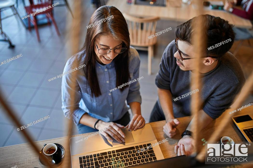 Stock Photo: Young man looking at smiling woman in a cafe with laptop.