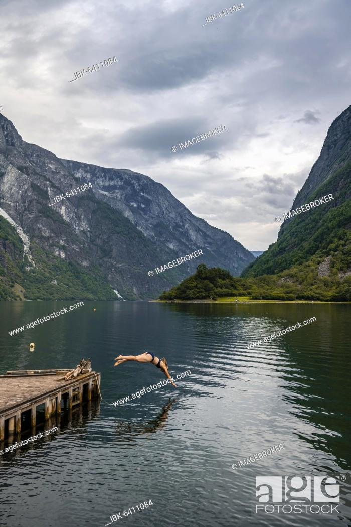 Stock Photo: Woman jumping into the water, Naeroyfjord, Aurland, Sogn og Fjordane, Norway, Europe.