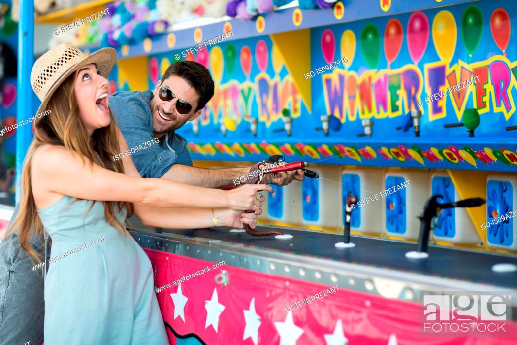 Stock Photo: Couple at fairground shooting gallery, Coney island, Brooklyn, New York, USA.