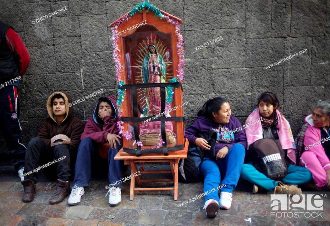 Stock Photo: Pilgrims sit by an image of the Virgin of Guadalupe at the pilgrimage to Our Lady of Guadalupe Basilica in Mexico City, Mexico, December 10, 2013.