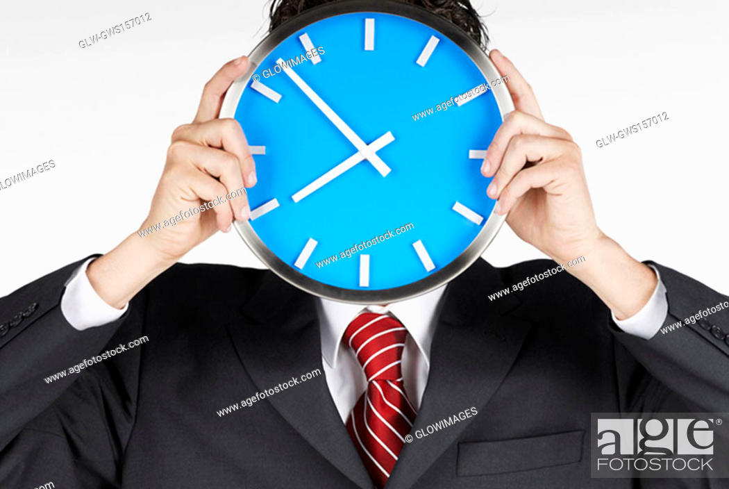 Stock Photo: Close-up of a businessman holding a clock in front of his face.