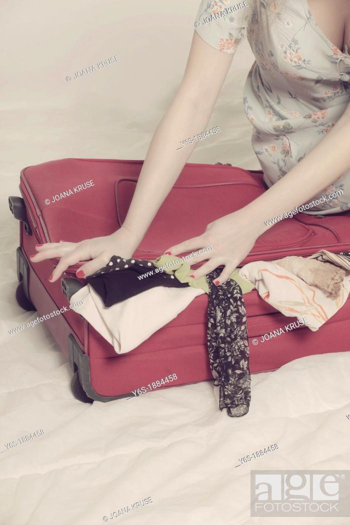 Stock Photo: a woman tries to close a suitcase.