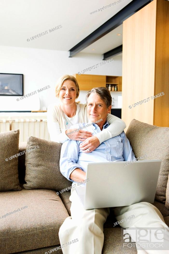 Stock Photo: Portrait of woman hugging man using laptop in living room.