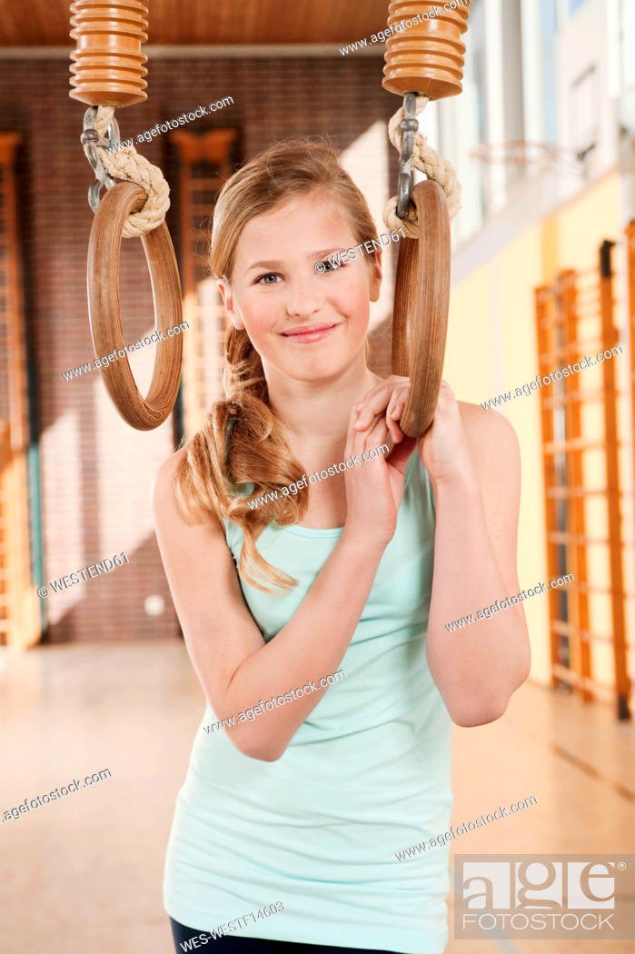 Stock Photo: Germany, Emmering, Girl 12-13 holding flying rings and smiling, portrait.