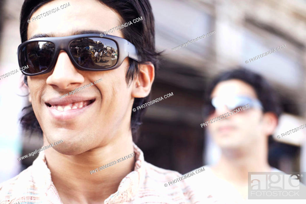 Stock Photo: Close-up of a young man wearing sunglasses and smiling.