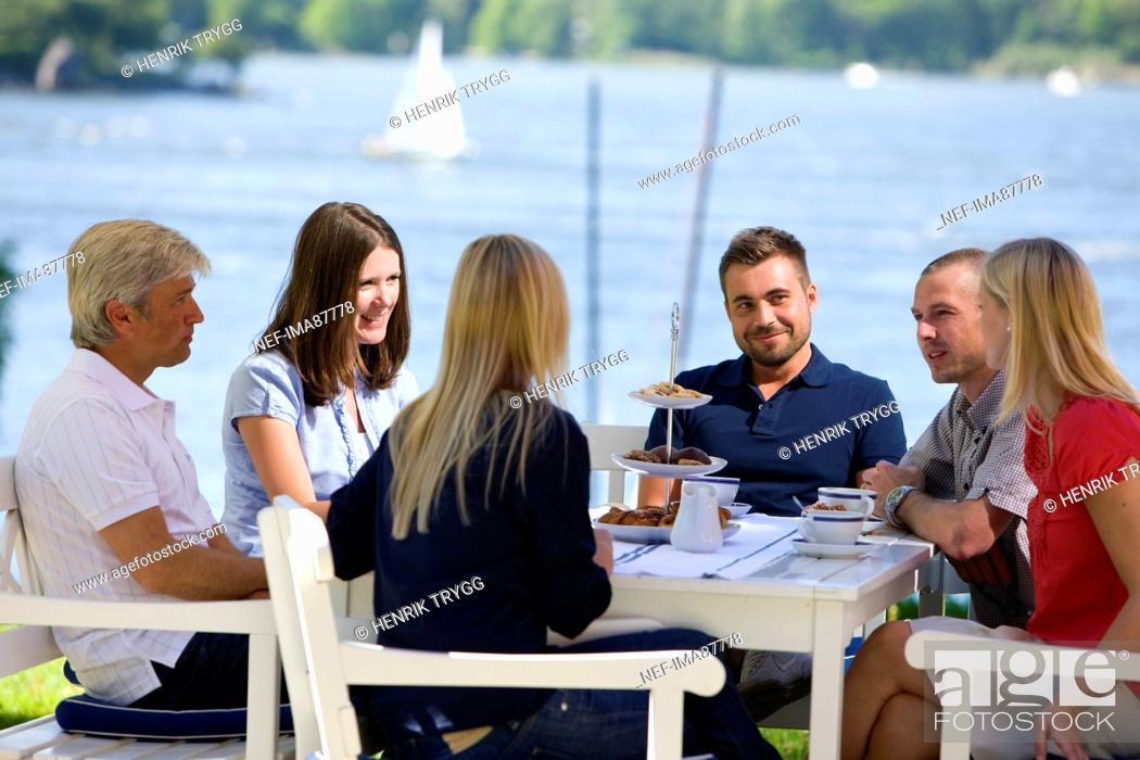 Stock Photo: Six people having coffee beside sea.