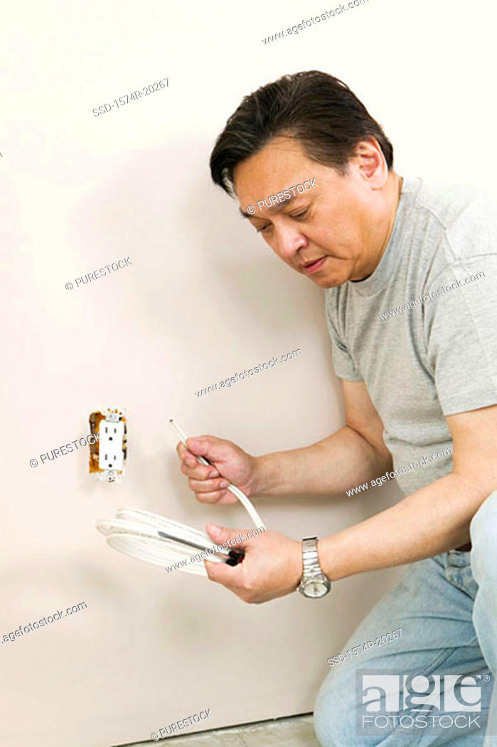 Stock Photo: Side profile of a mid adult man holding wire and a screwdriver near a power outlet.
