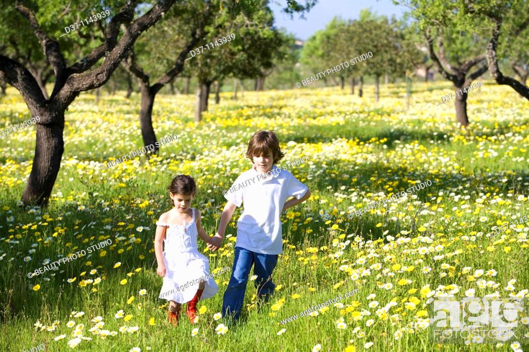 Stock Photo: A boy and a girl holding hands in a yellow flower field.