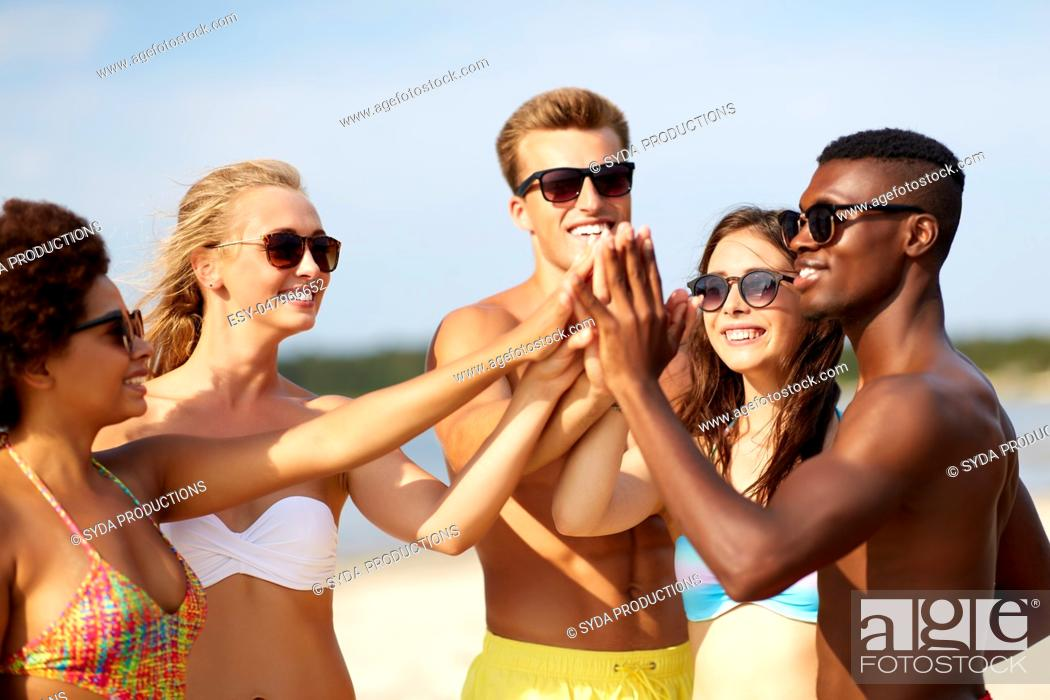 Stock Photo: happy friends making high five on summer beach.
