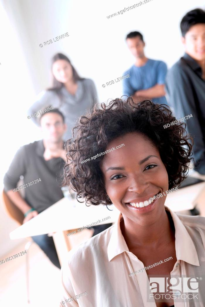 Stock Photo: Portrait of female office worker in front of colleagues.