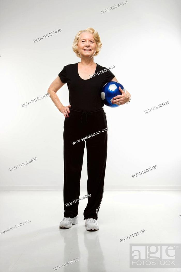 Stock Photo: Senior woman standing holding soccer ball.