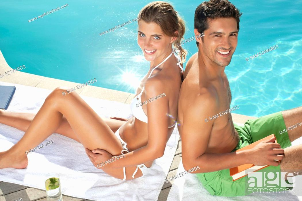 Stock Photo: Couple sitting back to back near swimming pool.