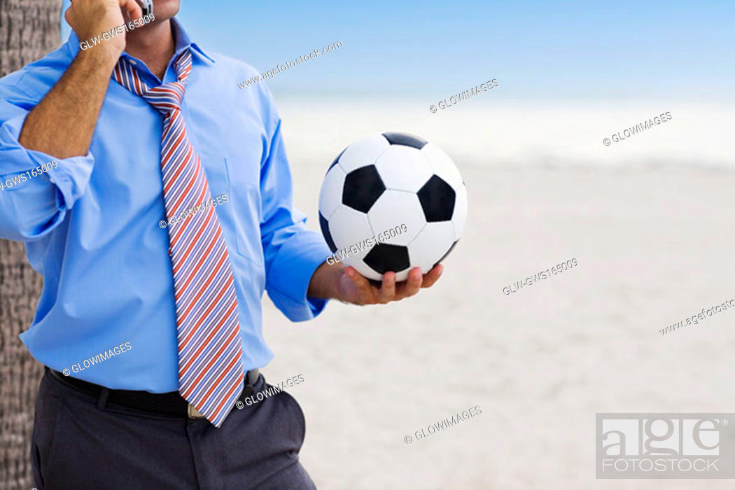 Stock Photo: Mid section view of a man holding a soccer ball and talking on a mobile phone.