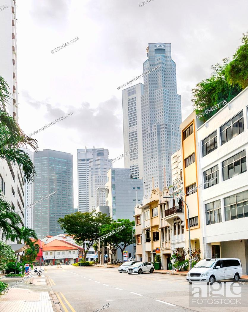 Stock Photo: City street of Singapore downtown with parked cars in hazy sunlight.