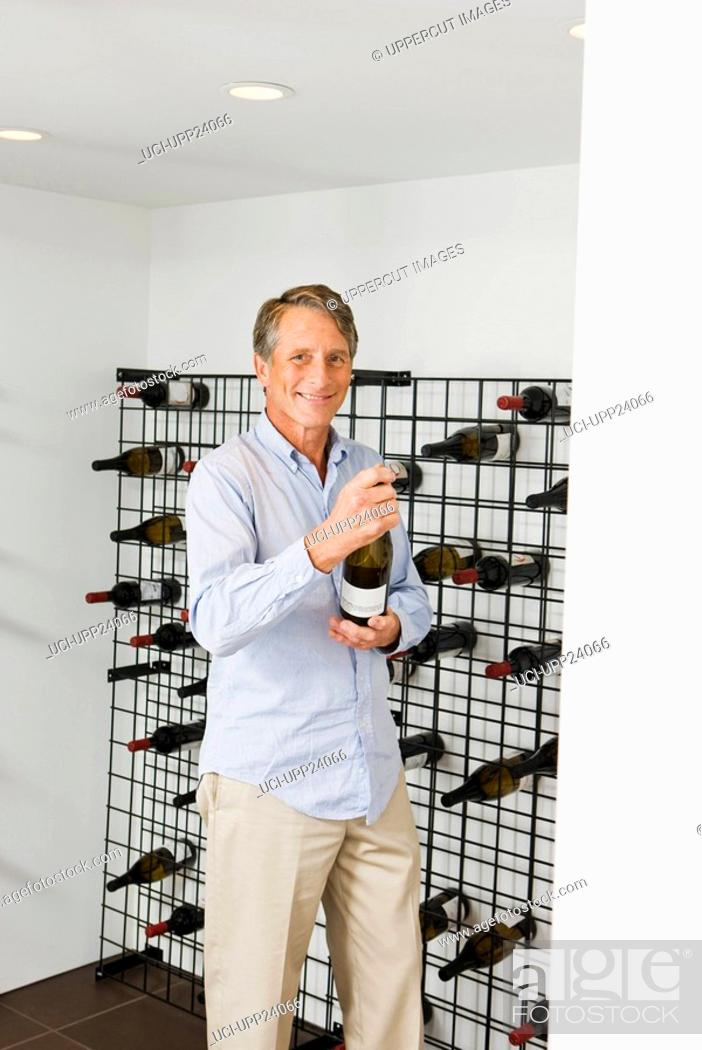 Stock Photo: Portrait of man selecting wine from wine rack.