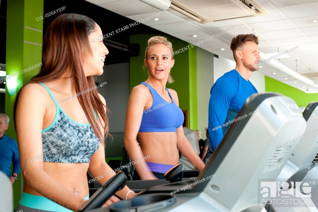 Stock Photo: People at gym using exercise machines chatting.