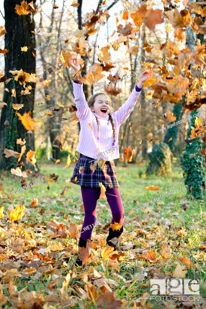 Stock Photo: girl is playing in the woods with autumn foliage.