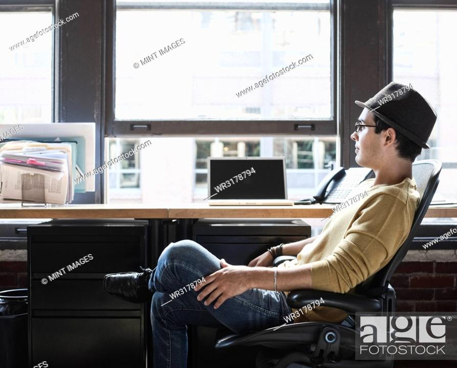 Stock Photo: Hispanic male at his office workstation in a creative office.