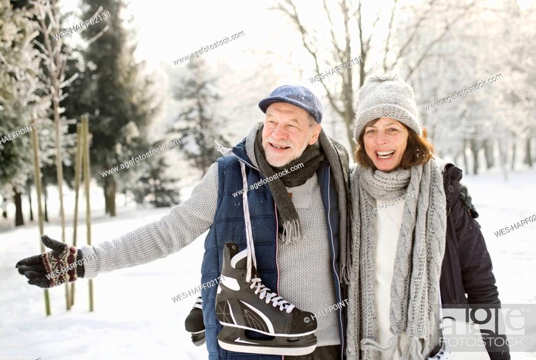 Photo de stock: Happy senior couple with ice skates in winter landscape.