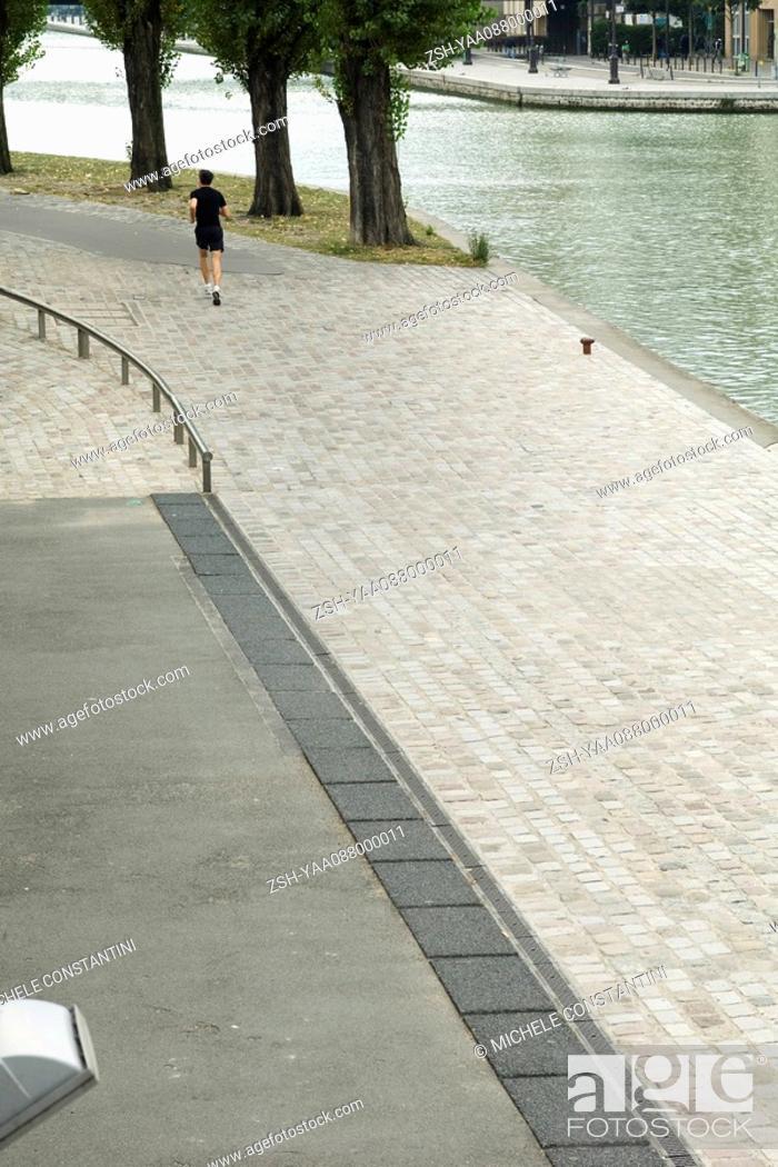 Stock Photo: France, Paris, Canal Saint-Martin, person jogging along water's edge.