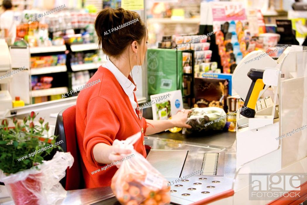 Stock Photo: Cashier totaling grocery purchases.