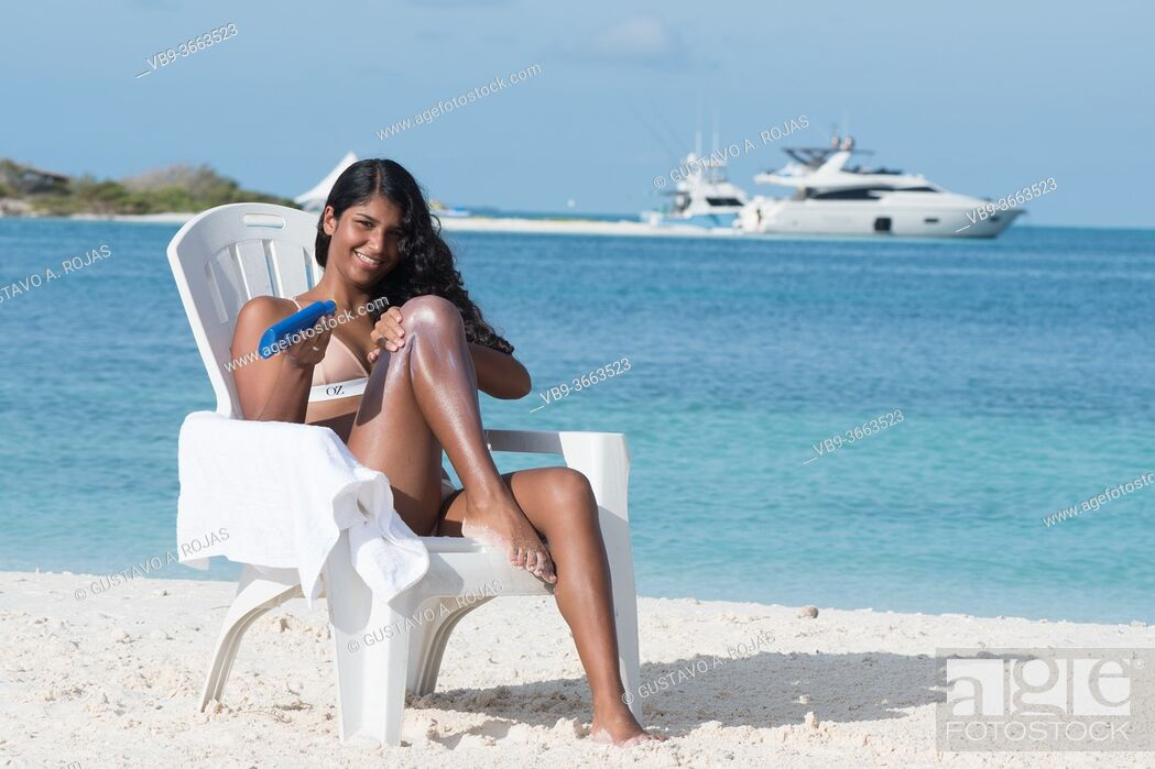 Stock Photo: YOUNG African American WOMAN apply sunscreen LOTION AT TROPICAL BEACH on the beach chair.