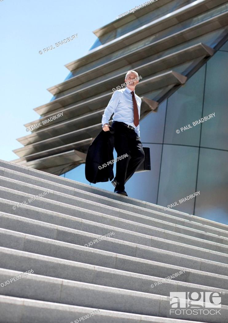 Stock Photo: Businessman walking down steps outdoors.