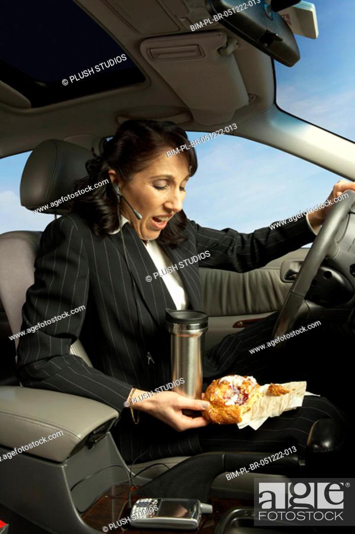 Stock Photo: Businesswoman driving and eating, San Rafael, California, United States.