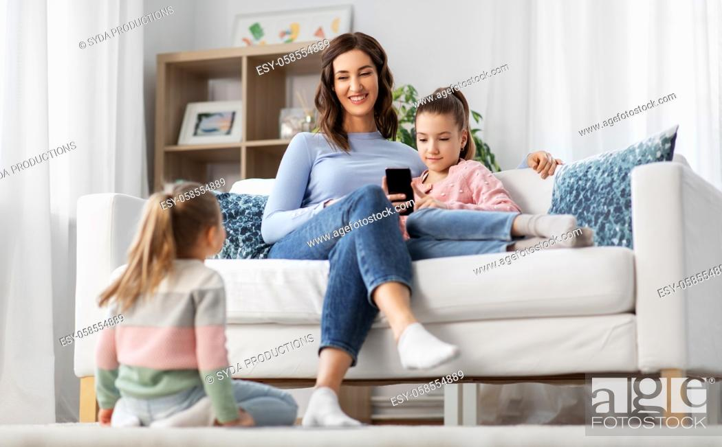 Stock Photo: happy mother and daughters with smartphone at home.