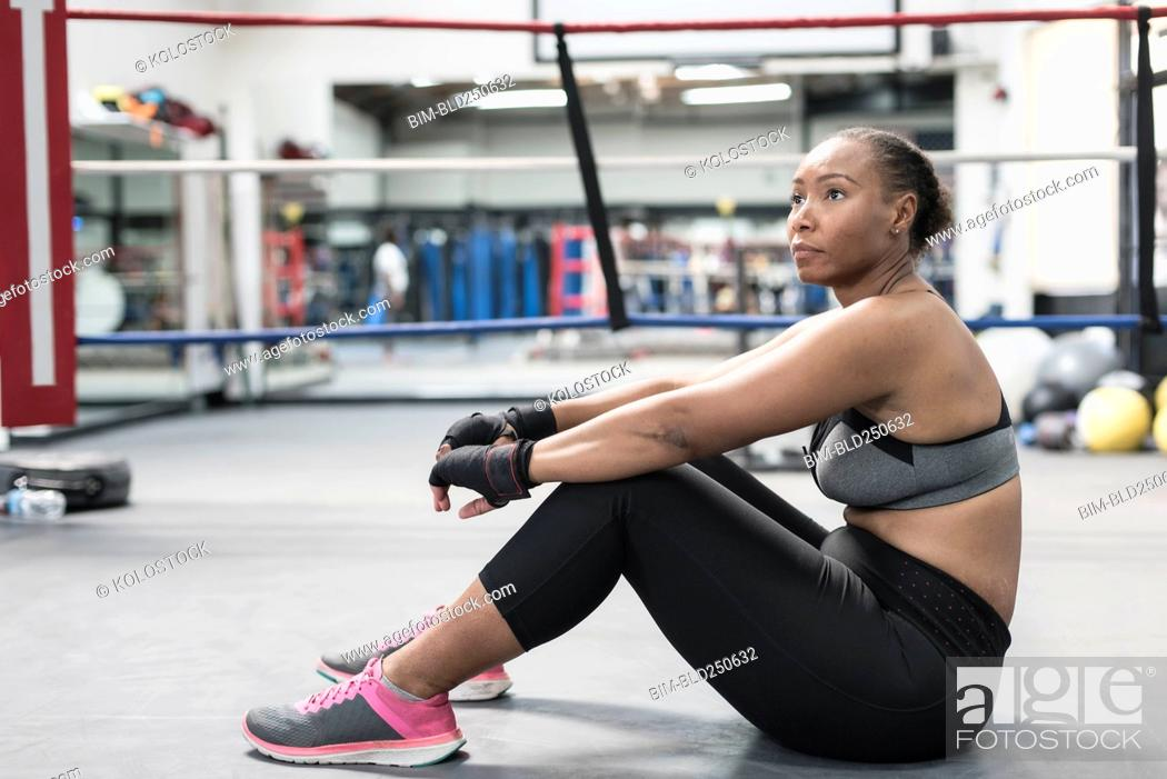 Stock Photo: Black woman sitting on floor in boxing ring.