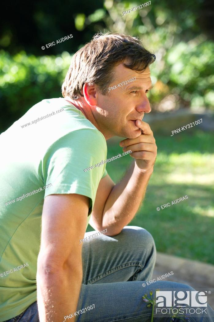 Stock Photo: Side profile of a mature man thinking with hand on chin.