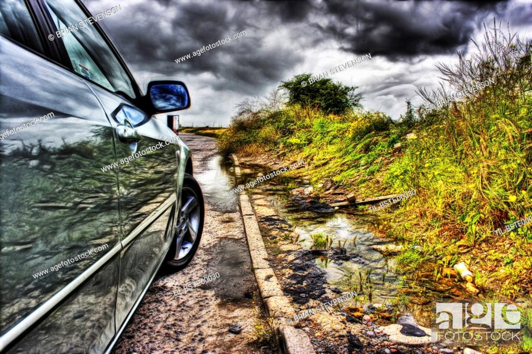 Stock Photo: Shiny reflections of some dumped roadside rubbish in the side of a mazda 6 with ominous moody stormy skies as a backdrop.