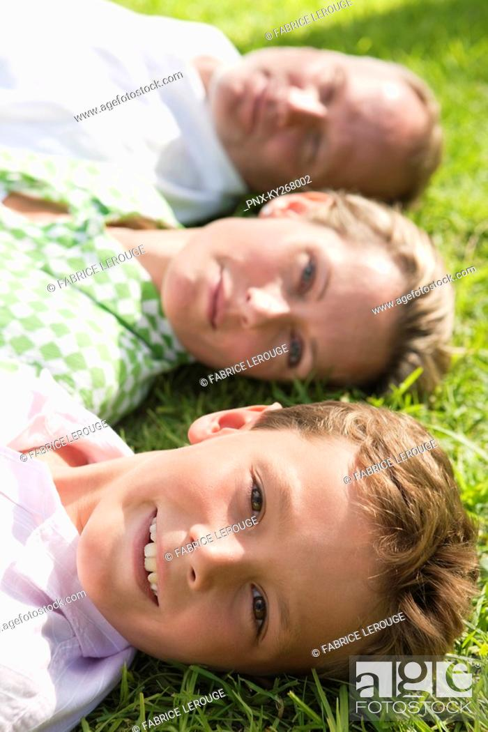 Stock Photo: Boy with his parents lying on grass in a park.
