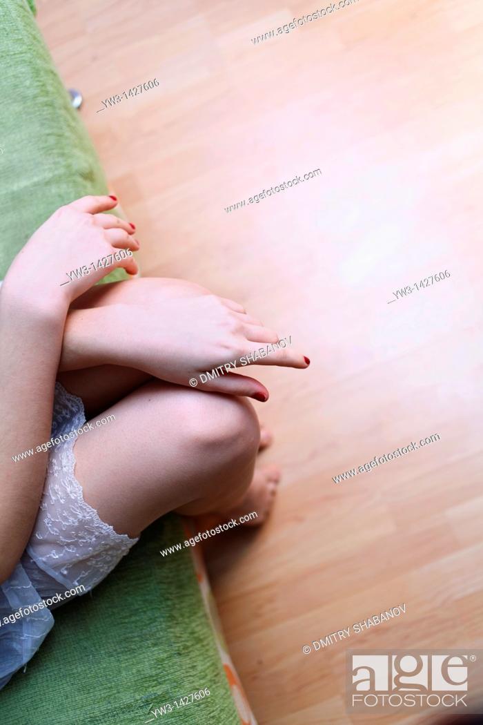 Stock Photo: Caucasian female bare legs indoors on sofa.