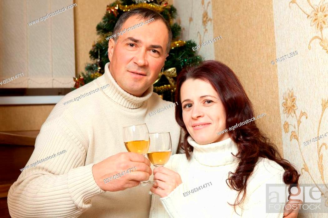 Stock Photo: Christmas Couple. Happy Smiling Family at home celebrating. New Year People. Middle-aged couple near a Christmas tree with glass of champagne in the interior of.
