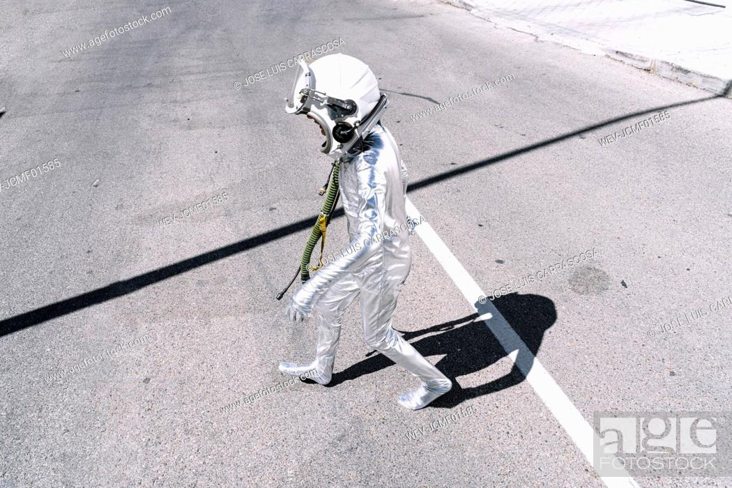 Stock Photo: Boy in astronaut costume walking on road in city.