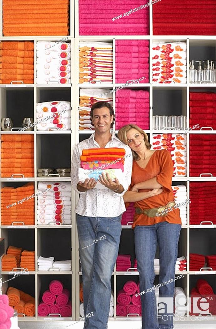 Stock Photo: Couple shopping in department store, woman leaning against boyfriend, man holding pile of folded towels, smiling, front view, portrait, shelves in background.