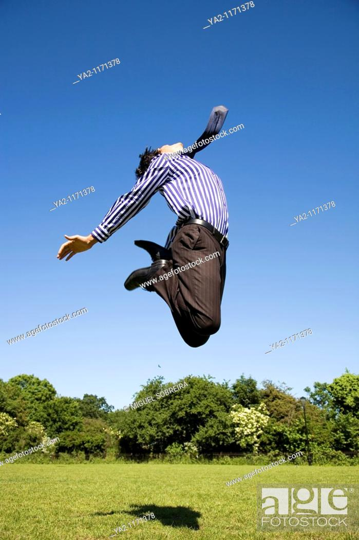 Stock Photo: Executive man jumping in the sky.