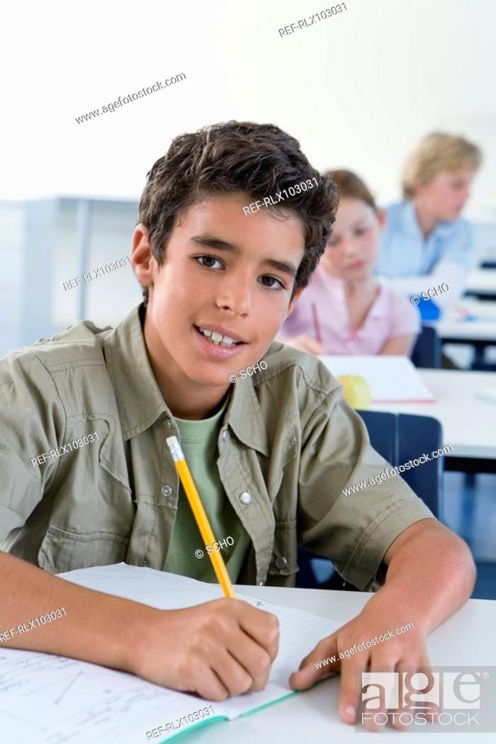 Stock Photo: School boy 10-13 writing in classroom, looking at camera.