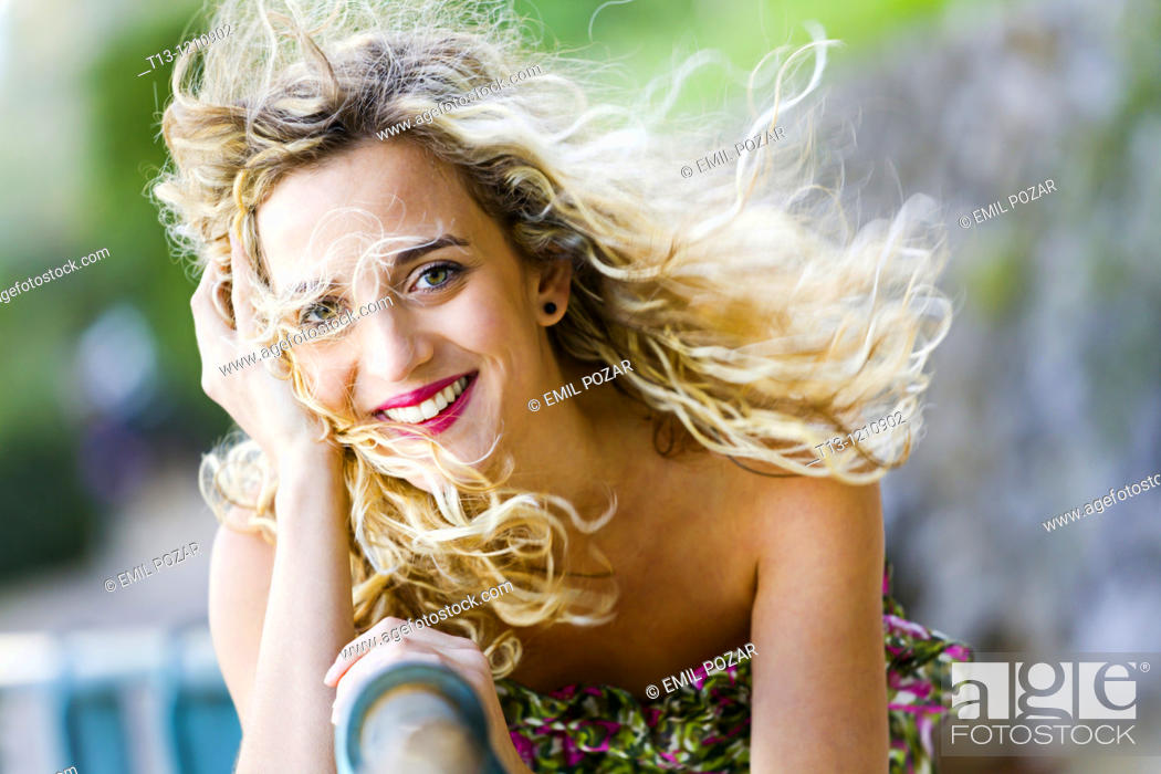 Stock Photo: Happy young woman with strong wind blowing her curly hair away.