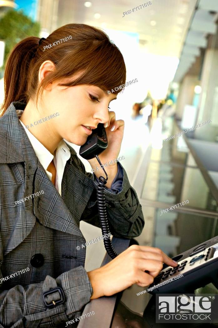 Stock Photo: Businesswoman talking on the telephone at an airport.